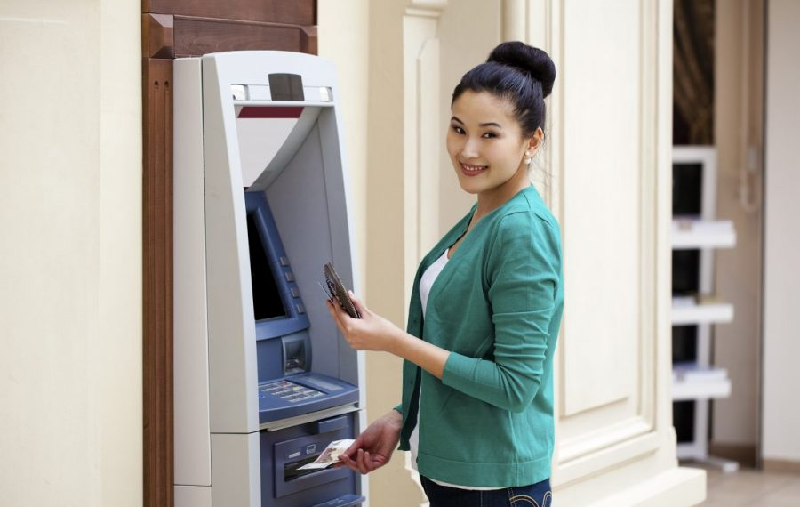Asian lady using an automated teller machine